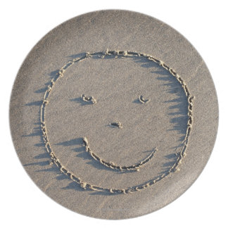 A smiley face drawn in sand. plates