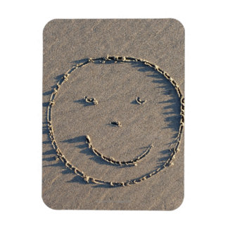 A smiley face drawn in sand. flexible magnet