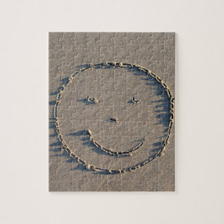 A smiley face drawn in sand. jigsaw puzzles
