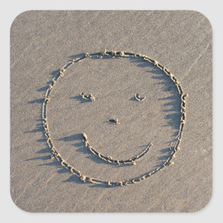 A smiley face drawn in sand. square sticker