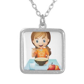 A smiling girl eating her breakfast pendants