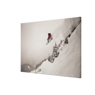 A snowboarder jumps off a cliff into powder in canvas print
