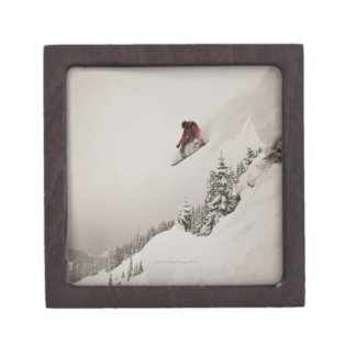 A snowboarder jumps off a cliff into powder in jewelry box