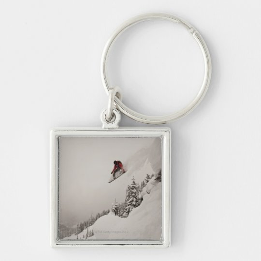 A snowboarder jumps off a cliff into powder in keychain