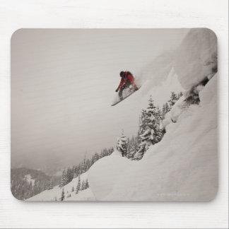 A snowboarder jumps off a cliff into powder in mouse pad