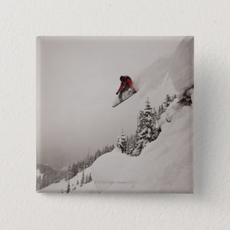 A snowboarder jumps off a cliff into powder in pinback button