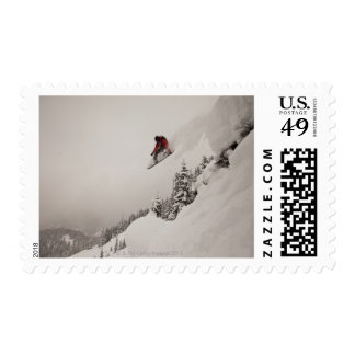 A snowboarder jumps off a cliff into powder in postage