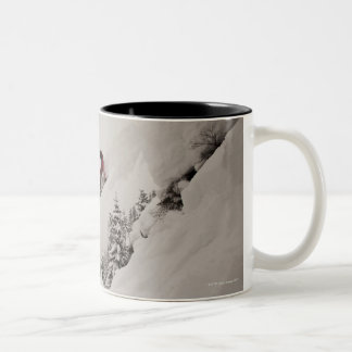 A snowboarder jumps off a cliff into powder in Two-Tone coffee mug