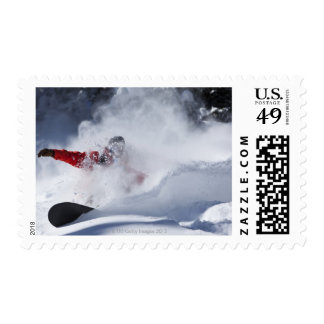 A snowboarder rips untracked powder turns in stamp