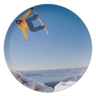 A snowboarder spins off a jump in Argentina Dinner Plate