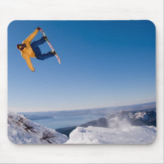 A snowboarder spins off a jump in Argentina Mouse Pad