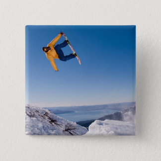A snowboarder spins off a jump in Argentina Pinback Button