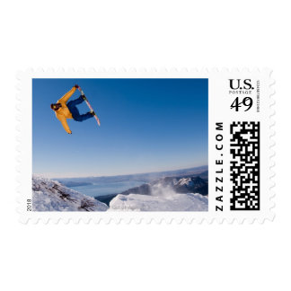 A snowboarder spins off a jump in Argentina Postage Stamp