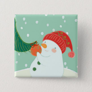 A snowman hanging an ornament on a tree pinback button