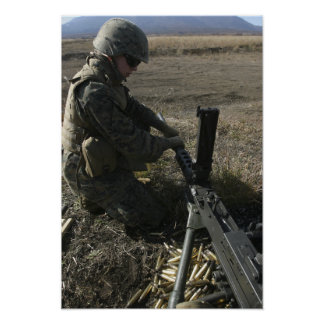 A soldier changes the barrel of an M2 50 Posters