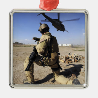 A soldier conducts security for an HH-60 Metal Ornament