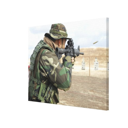 A soldier fires rounds down range canvas print