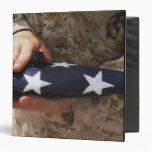 A soldier holds the United States flag Binder