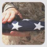 A soldier holds the United States flag Square Sticker