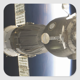 A Soyuz spacecraft backdropped by Earth Square Sticker