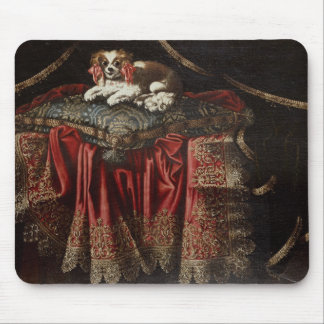 A spaniel seated on an embroidered cushion mouse pad