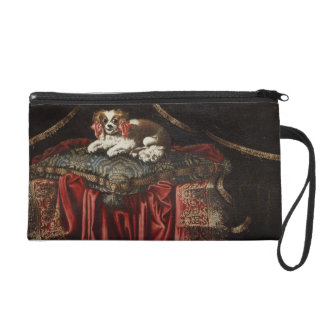 A spaniel seated on an embroidered cushion wristlet