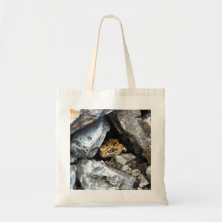 A spotted Frog hides among the rocks in a yard Tote Bag
