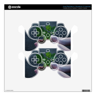 A sprout on a hand PS3 controller decals