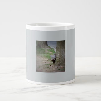 A squirrel on a tree root large coffee mug