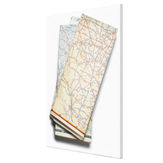 A stack of folded road maps on a white canvas print