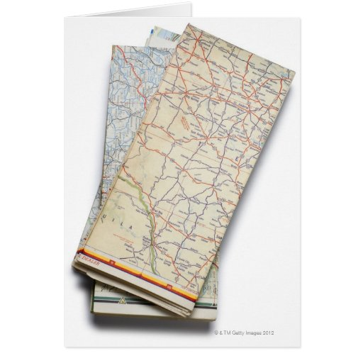 A stack of folded road maps on a white greeting card
