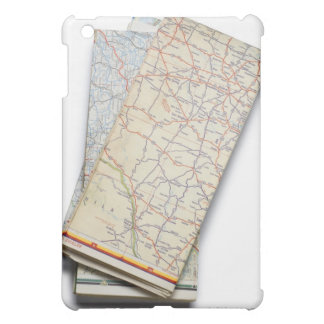 A stack of folded road maps on a white iPad mini covers