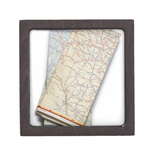 A stack of folded road maps on a white keepsake box