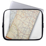 A stack of folded road maps on a white laptop sleeves