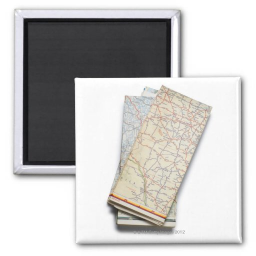 A stack of folded road maps on a white fridge magnet