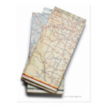 A stack of folded road maps on a white post card