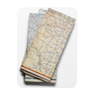 A stack of folded road maps on a white vinyl magnet