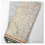 A stack of folded road maps on a white tiles