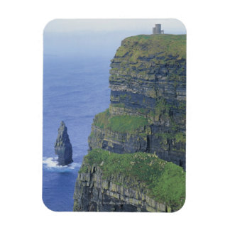 a stone castle standing on top a steep cliff in rectangular photo magnet