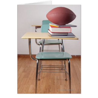 A student desk with a football sitting on a pile card