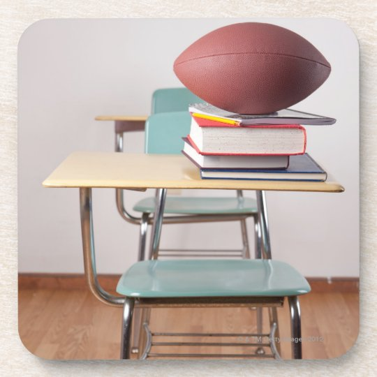 A student desk with a football sitting on a pile drink coaster
