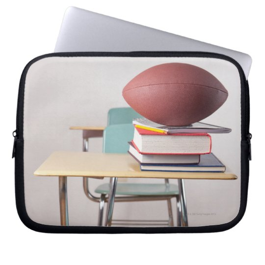 A student desk with a football sitting on a pile laptop sleeve