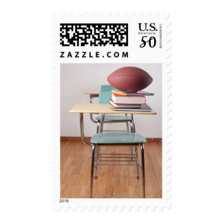 A student desk with a football sitting on a pile postage