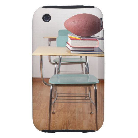 A student desk with a football sitting on a pile tough iPhone 3 cover