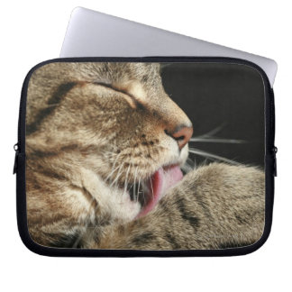 A tabby cat licking his paw. computer sleeve