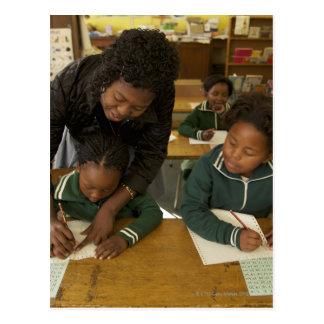 A teacher assists young schoolchildren in her postcard