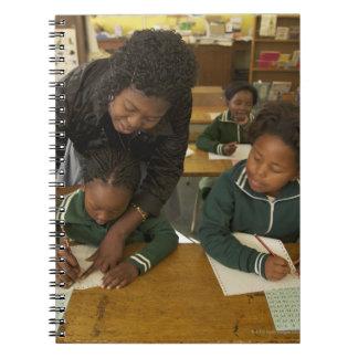 A teacher assists young schoolchildren in her spiral notebook