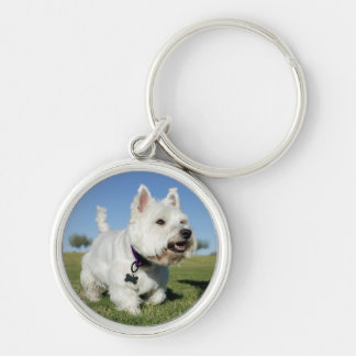 A Terrier playing out in the field Keychain