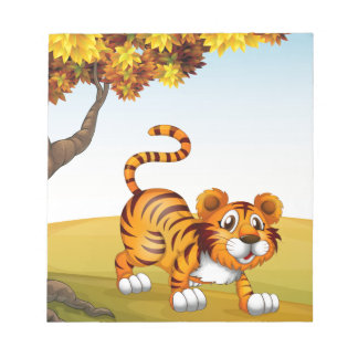 A tiger in a jumping position near the big tree notepads