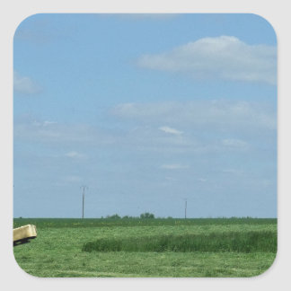 a tractor cutting wheat fields and a water tower square sticker